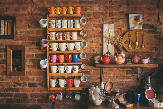 assorted color mugs on brown wooden floating rack