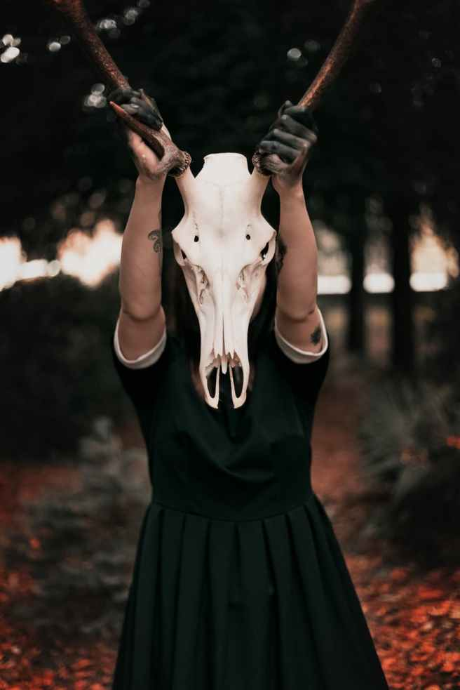 person wearing black dress while holding skull mask with horns