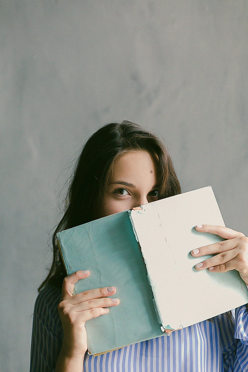 woman in blue striped flannel shirt holding a book indoors