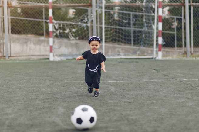 cute little boy with football ball on sports ground